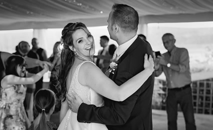 Bride smiling to the camera while dancing with groom