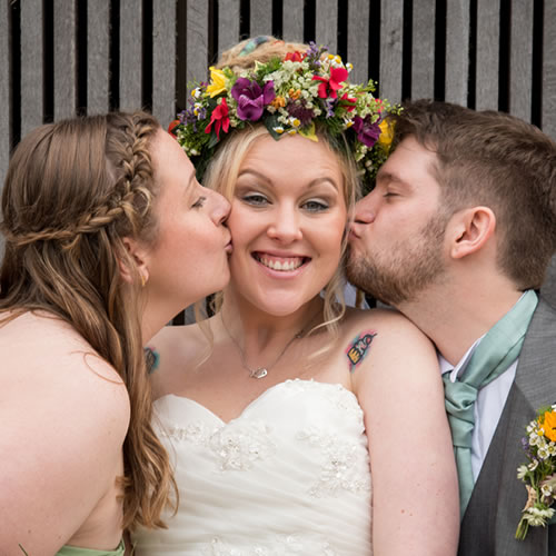 Bride kissed by groom and bridesmaid